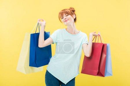 Photo pour Sourire rousse fille tenant des sacs à provisions avec les yeux fermés isolé sur jaune - image libre de droit