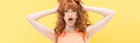 Foto de Foto panorámica de la mujer rizada conmocionado tocando el pelo y mirando la cámara aislada en amarillo - Imagen libre de derechos