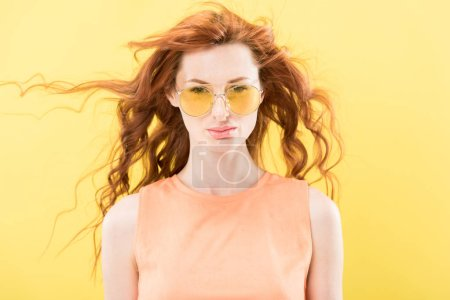 Photo for Front view of serious curly redhead woman in sunglasses isolated on yellow - Royalty Free Image