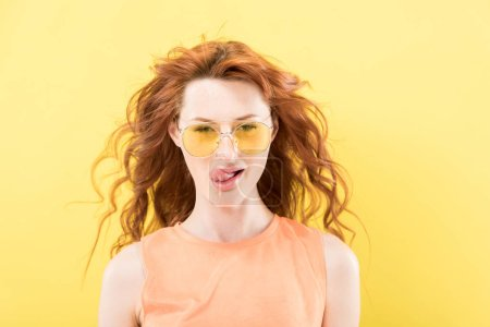 Photo for Front view of curly redhead woman in sunglasses licking lips isolated on yellow - Royalty Free Image