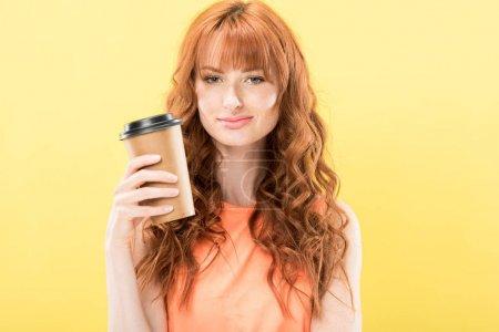 Photo pour Vue de face de fille rousse souriante bouclée tenant tasse en papier de café isolé sur jaune - image libre de droit