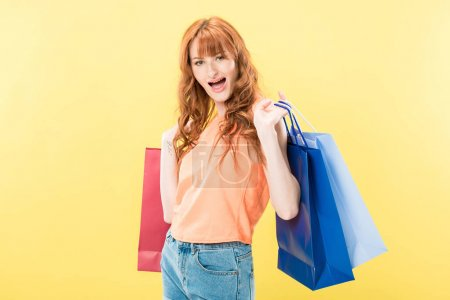 smiling excited redhead girl holding shopping bags and looking at camera isolated on yellow