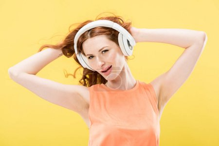 Photo for Attractive redhead woman listening music in headphones and touching curly hair isolated on yellow - Royalty Free Image