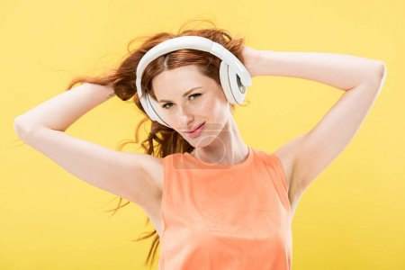 Foto de Atractiva mujer pelirroja escuchando música en auriculares y tocando el pelo rizado aislado en amarillo - Imagen libre de derechos