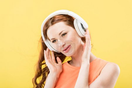 Photo for Attractive redhead woman listening music in headphones and smiling isolated on yellow - Royalty Free Image