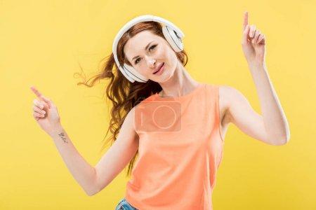 Foto de Atractiva mujer pelirroja sonriente escuchando música en auriculares y bailando aislado en amarillo - Imagen libre de derechos