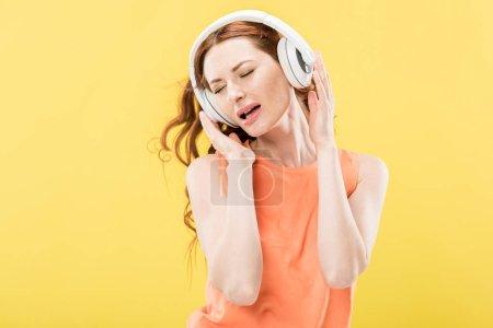 Photo pour Femme attirante d'écoute de la voix dans le casque et chantant d'isolement sur le jaune - image libre de droit