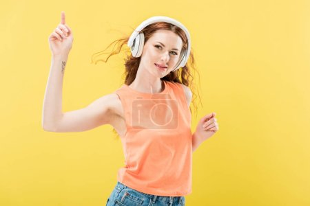 Photo for Attractive smiling redhead woman listening music in headphones and dancing isolated on yellow - Royalty Free Image