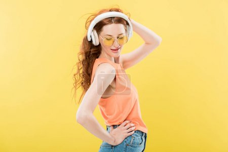 Photo for Attractive redhead woman in sunglasses listening music in headphones and smiling isolated on yellow - Royalty Free Image