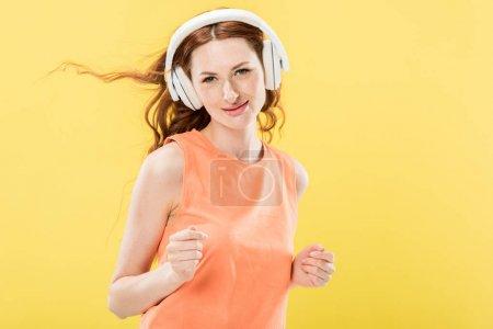 Photo pour Vue avant de la femme attirante de femme de rousse écoutant la musique dans le casque et souriant isolé sur le jaune - image libre de droit