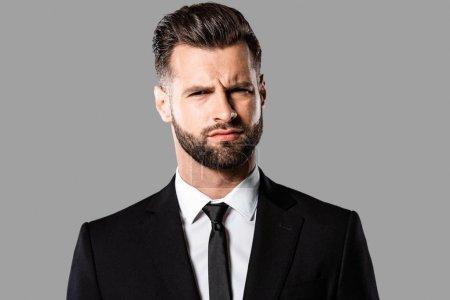 Photo pour Beau homme d'affaires sceptique en costume noir isolé sur gris - image libre de droit