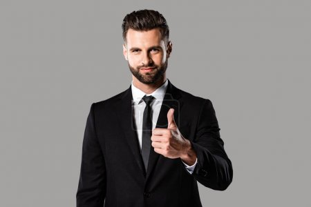Photo for Smiling handsome businessman in black suit showing thumb up isolated on grey - Royalty Free Image