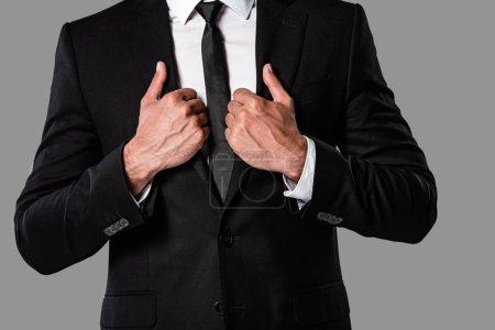 Ausgeschnittene Ansicht des Geschäftsmannes im schwarzen Anzug mit Händen auf Jacke isoliert auf grau