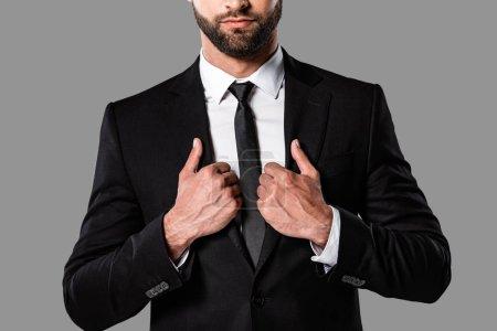 Foto de Vista recortada de elegante hombre de negocios barbudo en traje negro aislado en gris - Imagen libre de derechos