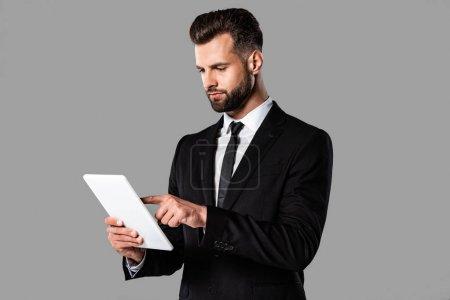 Photo pour Beau homme d'affaires dans le procès noir utilisant la tablette numérique d'isolement sur le gris - image libre de droit