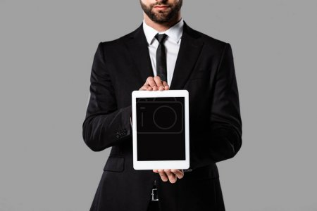 partial view of businessman in black suit showing digital tablet with blank screen isolated on grey