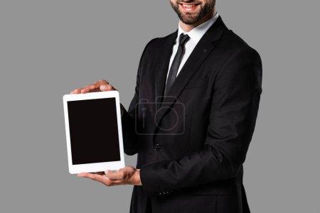 recortado vista de sonriente hombre de negocios en traje negro mostrando tableta digital con pantalla en blanco aislado en gris