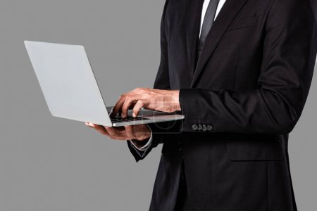 cropped view of businessman in black suit using laptop isolated on grey