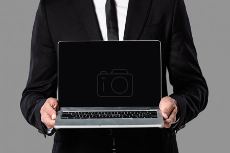 Photo for Cropped view of businessman in black suit showing laptop with blank screen isolated on grey - Royalty Free Image