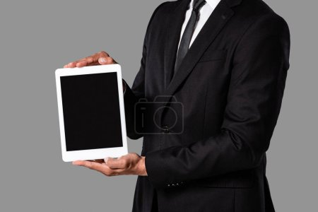 Photo for Cropped view of businessman in black suit showing digital tablet with blank screen isolated on grey - Royalty Free Image