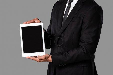 Photo pour Vue recadrée de l'homme d'affaires dans le procès noir affichant la tablette numérique avec l'écran blanc d'isolement sur le gris - image libre de droit