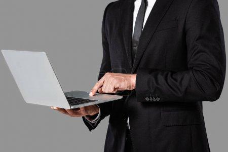 Photo pour Vue partielle de l'homme d'affaires en costume noir en utilisant un ordinateur portable isolé sur gris - image libre de droit