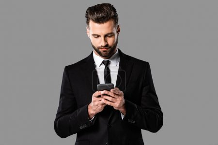 Photo for Bearded businessman in black suit using smartphone isolated on grey - Royalty Free Image