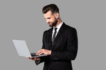 Photo pour Homme d'affaires beau de sourire dans le procès noir utilisant l'ordinateur portatif d'isolement sur le gris - image libre de droit