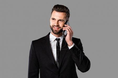 Photo pour Bel homme d'affaires souriant en costume noir parlant sur smartphone isolé sur gris - image libre de droit