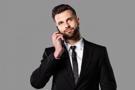 homme d'affaires beau et rêveur en costume noir parlant sur smartphone isolé sur gris