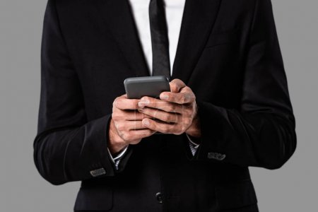 Photo for Partial view of businessman in black suit using smartphone isolated on grey - Royalty Free Image