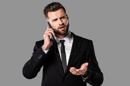 Foto de Hombre de negocios confundido en traje negro hablando en el teléfono inteligente y mostrando gesto de encogimiento de hombros aislado en gris - Imagen libre de derechos