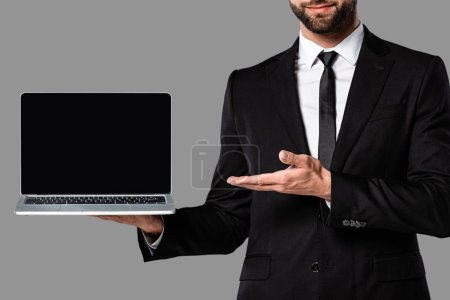 Photo for Cropped view of businessman in black suit pointing with hand at laptop with blank screen isolated on grey - Royalty Free Image