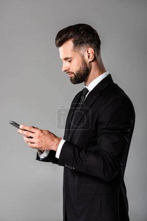 Foto de Vista lateral de apuesto hombre de negocios en traje negro usando teléfono inteligente aislado en gris - Imagen libre de derechos