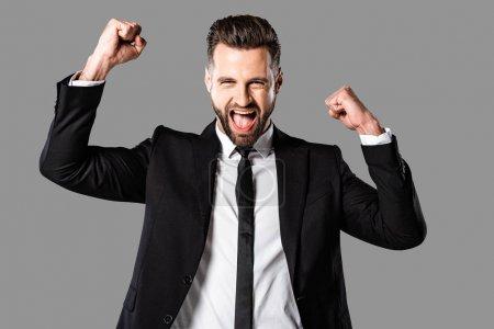 Foto de Hombre de negocios feliz en traje negro que muestra sí gesto aislado en gris - Imagen libre de derechos