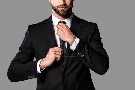 Photo pour Vue recadrée de élégant bel homme d'affaires en costume noir fixation cravate isolé sur gris - image libre de droit