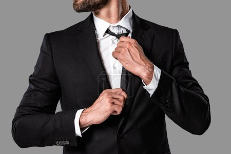 Photo pour Vue recadrée de élégant bel homme d'affaires en costume noir touchant cravate isolé sur gris - image libre de droit