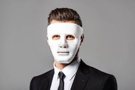 Photo pour Mystérieux homme d'affaires en costume noir et masque blanc isolé sur gris - image libre de droit