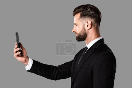 Photo for Side view of handsome businessman in black suit taking selfie on smartphone isolated on grey - Royalty Free Image