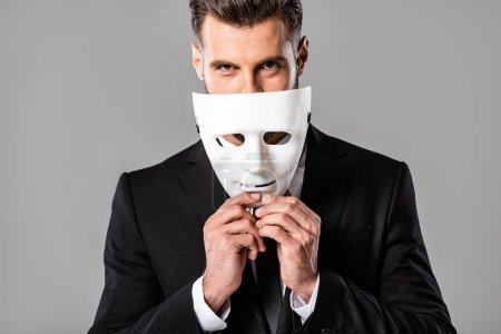 Photo pour Bel homme d'affaires rusé en costume noir décollant masque blanc isolé sur gris - image libre de droit