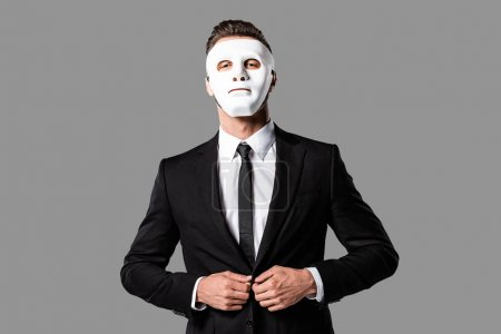 confident handsome businessman in black suit and white mask isolated on grey
