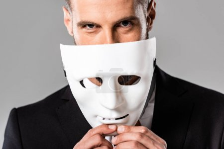 cunning businessman in black suit taking off white mask isolated on grey