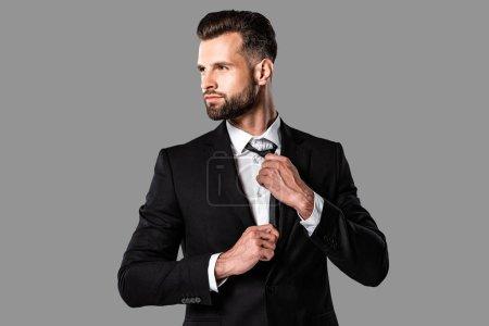 Photo pour Élégant homme d'affaires élégant en costume noir regardant loin isolé sur gris - image libre de droit