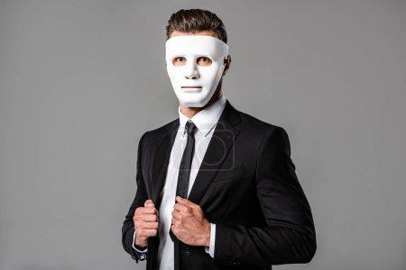 Photo pour Homme d'affaires en costume noir et masque blanc isolé sur gris - image libre de droit