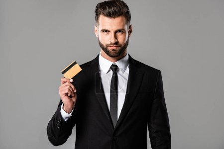 Photo for Handsome bearded businessman in black suit holding credit card isolated on grey - Royalty Free Image