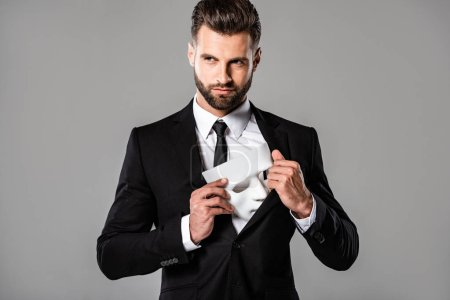 sly businessman in black suit hiding white mask isolated on grey