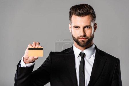 Photo pour Homme d'affaires confiant dans le costume noir retenant la carte de crédit d'isolement sur le gris - image libre de droit