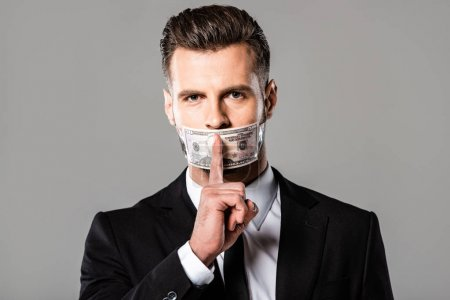 Photo for Businessman in black suit with dollar banknote on mouth showing hush gesture isolated on grey - Royalty Free Image