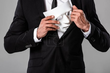 Photo pour Vue partielle d'homme d'affaires dans le procès noir retenant le masque blanc d'isolement sur le gris - image libre de droit