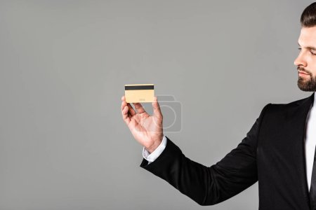 Photo for Businessman in black suit showing credit card isolated on grey - Royalty Free Image
